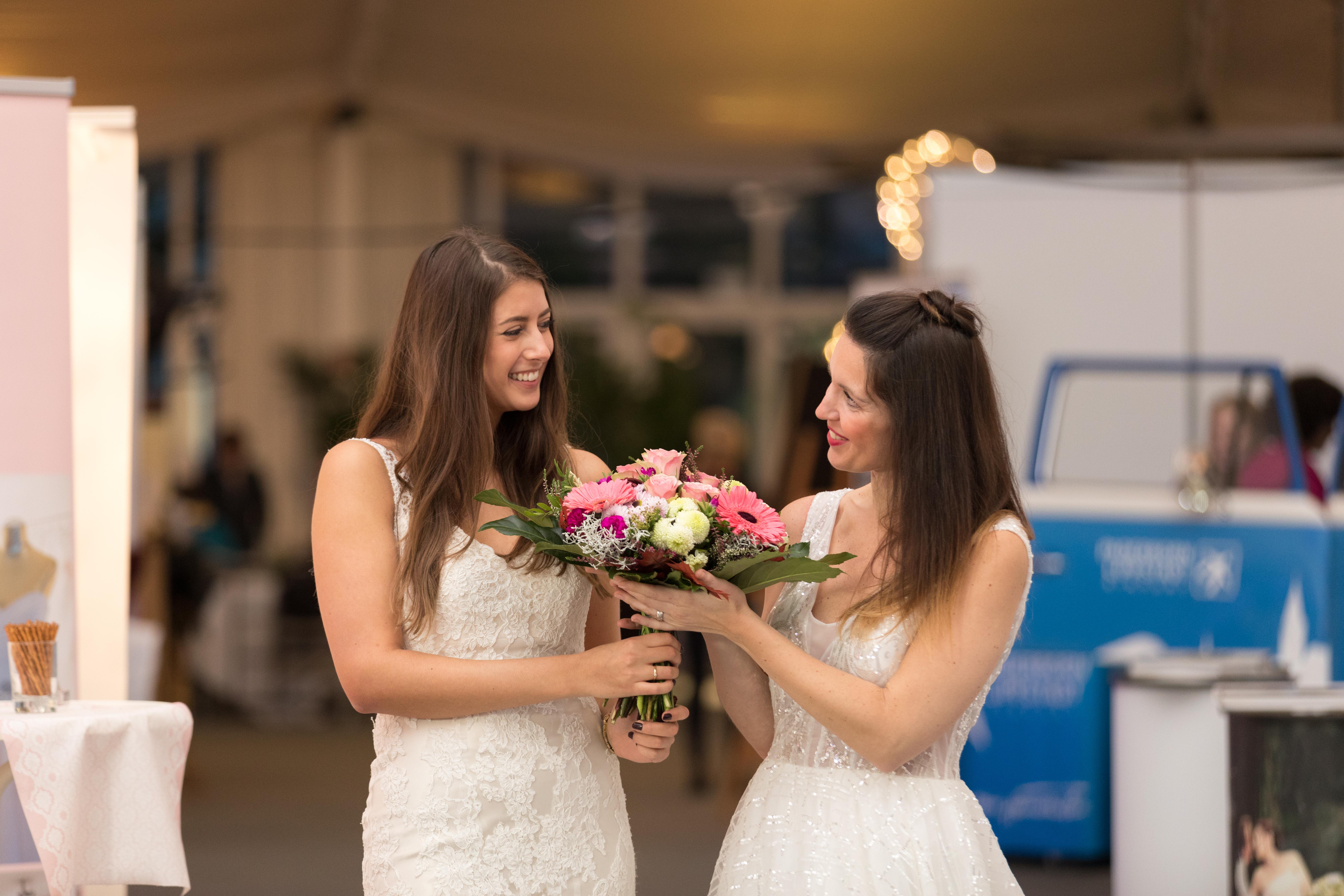 Zwei Bräute halten den Blumenstrauß